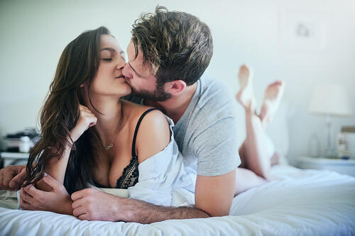 couple kissing passionately in bed